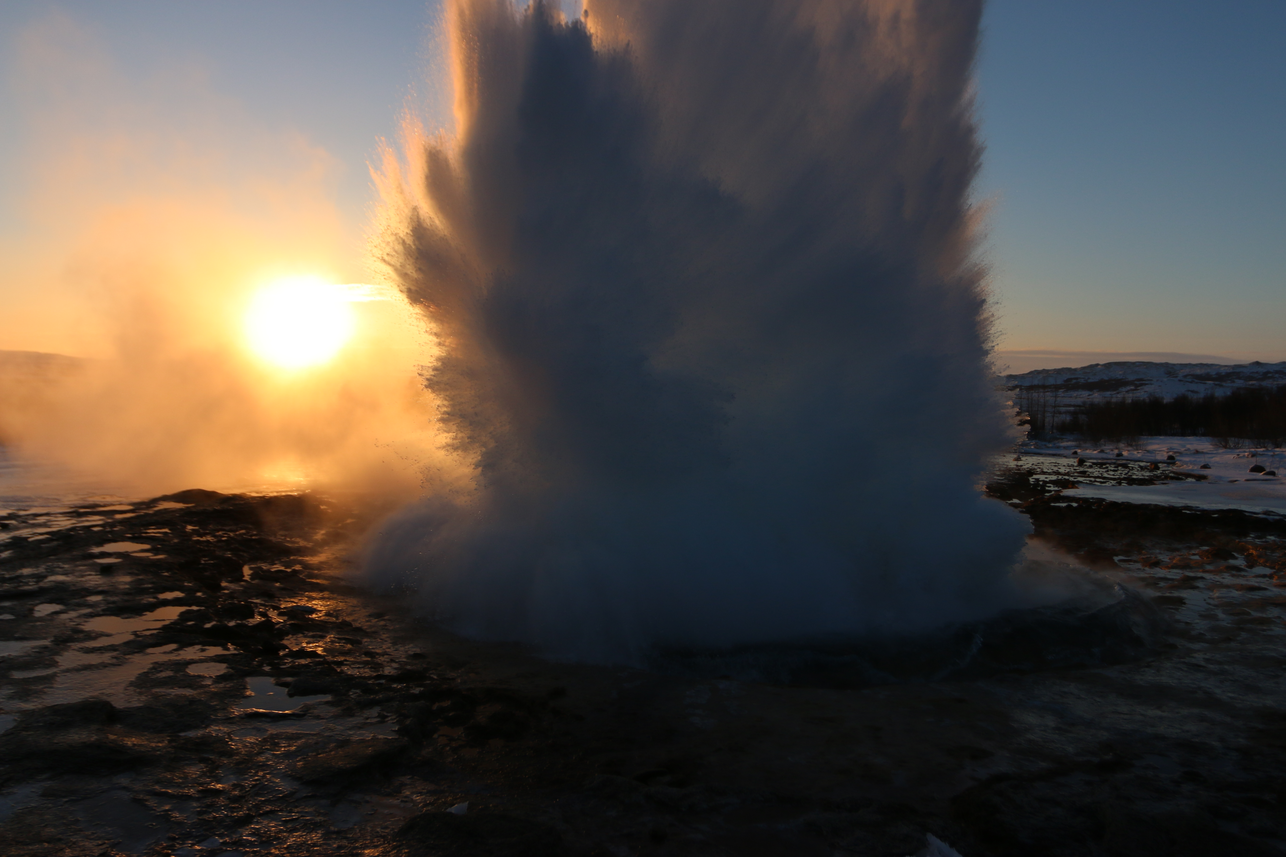 Geysir exploding in front of Iceland's perfect, if ephemeral, golden winter sun.